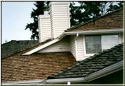 "This is a great photograph depicting the differences between a ""treated"" roof and an ""untreated"" roof after two years since construction of all three roofs."